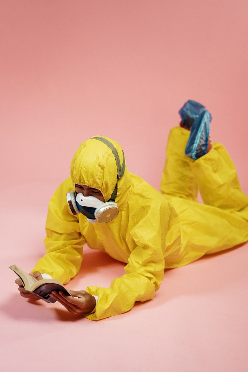 person in yellow coveralls reading a book